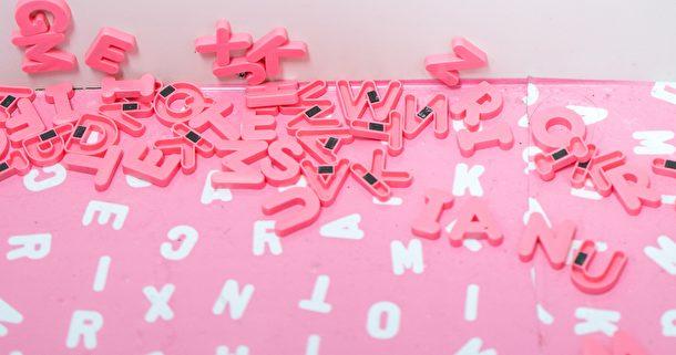 Rosa bokstäver på en tavla.